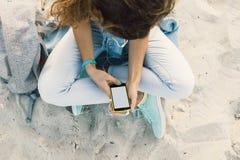 Giovane castana esile si siede sulla spiaggia in jeans e sull'ascolto Fotografie Stock Libere da Diritti