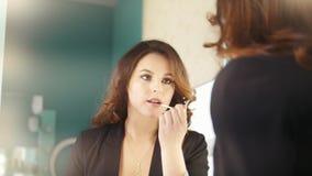 Giovane castana in labbra di bellezza di una coloritura del salone che stanno davanti allo specchio stock footage