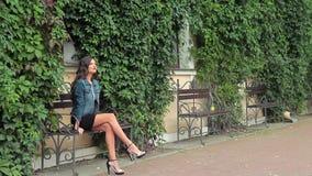 Giovane castana snello sta sedendosi su un banco, sullo sguardo intorno e sul sorridere archivi video