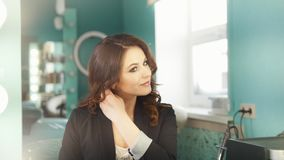Giovane castana in un salone di bellezza che corregge le labbra dei capelli che stanno davanti allo specchio video d archivio