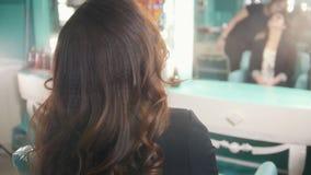 Giovane castana in un salone di bellezza, parrucchiere spruzza la lacca stock footage