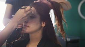 Giovane castana in un salone di bellezza, truccatore che fa il trucco e che contorna, il parrucchiere fa la designazione archivi video