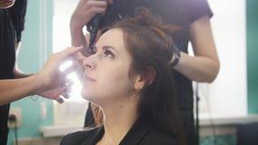 Giovane castana in un salone di bellezza, truccatore che fa il trucco, il parrucchiere fa la designazione stock footage