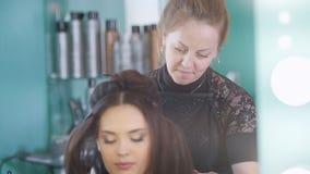 Giovane castana in un salone di bellezza, truccatore che fa il trucco, il parrucchiere fa la designazione archivi video