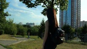 Giovane castana in vestito nero e con uno zaino cammina giù la via stock footage