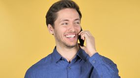Giovane casuale che parla sul telefono su fondo giallo archivi video