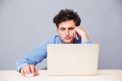 Giovane casuale che per mezzo del computer portatile Immagine Stock