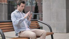 Giovane casuale facendo uso della seduta dello smartphone all'aperto video d archivio