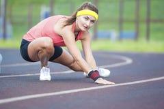 Giovane Caucasian Sporstwoman che ha allungamento degli esercizi sullo stadio all'aperto Immagine Stock