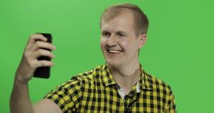 Giovane caucasico in camicia gialla che prende i selfies piacevoli sullo smartphone stock footage