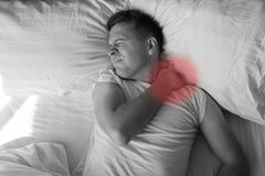 Giovane caucasico che ha dolore terribile in collo a letto di mattina Fotografie Stock