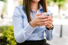 Giovane cellulare di uso della donna di affari all'aperto fotografie stock