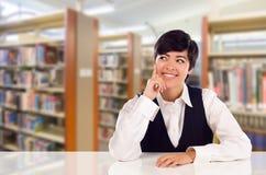 Giovane cercare di Daydreaming In Library dello studente della corsa mista Immagini Stock Libere da Diritti