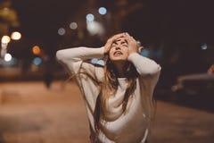 Giovane cercare di grido sollecitato emozionale della donna, via della città nella notte, uguagliante accende il fondo del bokeh  Fotografia Stock