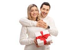 Giovane che abbraccia una giovane donna che tiene un contenitore di regalo avvolto fotografia stock libera da diritti