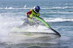 Giovane che accelera avanti sul jetbike durante la corsa fotografia stock