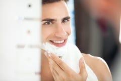 Giovane che applica crema da barba al suo fronte immagine stock