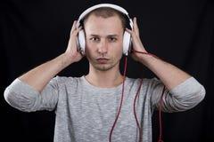 Giovane che ascolta intento la musica sulle cuffie e che guarda fisso i Immagini Stock