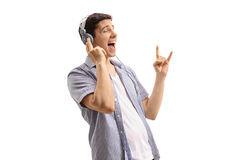Giovane che ascolta la musica e che fa gesto di mano della roccia Fotografia Stock Libera da Diritti