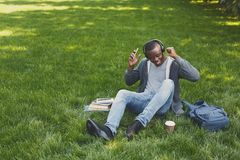 Giovane che ascolta la musica su erba all'aperto Fotografie Stock