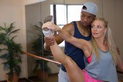 Giovane che assiste ballerino nell'allungamento della gamba Fotografia Stock