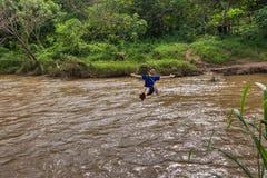 Giovane che attraversa il fiume sulla linea dello zip in Chiang Mai fotografia stock libera da diritti