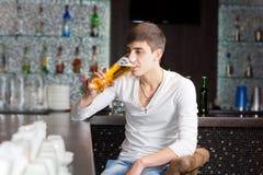 Giovane che beve in un pub Immagini Stock Libere da Diritti