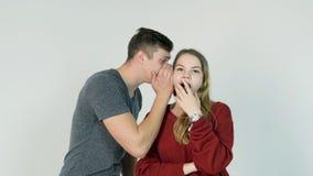 Giovane che bisbiglia un segreto ad una giovane donna sorpresa Il giovane dice un segreto alla ragazza fotografie stock