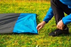 Giovane che blocca una coperta di nylon impermeabile per il riposo sull'erba, con i pali o i pioli di plastica gialli della tenda immagine stock libera da diritti
