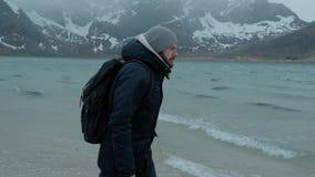 Giovane che cammina da solo sulla spiaggia un giorno di inverno Forte vento stock footage