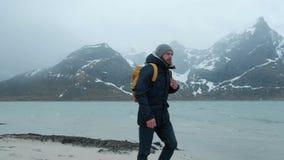 Giovane che cammina da solo sulla spiaggia un giorno di inverno Forte vento archivi video