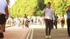 Giovane che cammina e che parla sul telefono in un parco archivi video