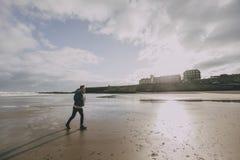 Giovane che cammina lungo la spiaggia di inverno Immagine Stock