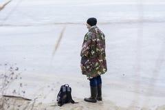 Giovane che cammina sulla spiaggia che guarda l'acqua congelata in un cappotto di pioggia militare Immagine Stock