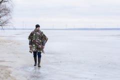 Giovane che cammina sulla spiaggia che guarda l'acqua congelata in un cappotto di pioggia militare Fotografia Stock