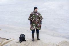 Giovane che cammina sulla spiaggia che guarda l'acqua congelata in un cappotto di pioggia militare Fotografia Stock Libera da Diritti
