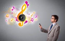 Giovane che canta e che ascolta la musica con le note musicali Immagine Stock