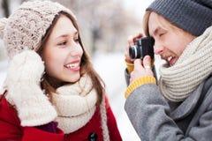 Giovane che cattura foto della donna nell'inverno Fotografie Stock