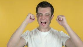 Giovane che celebra successo isolato su fondo giallo stock footage