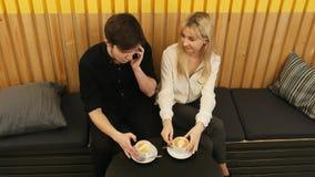 Giovane che chiama dal telefono cellulare, mentre sedendosi in caffè con l'amica Immagine Stock