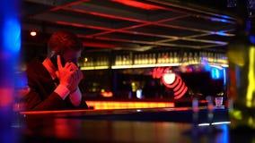 Giovane che chiama taxi, sedentesi nella barra da solo dopo il partito, rischio di azionamento ubriaco stock footage