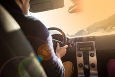 Giovane che conduce la sua automobile ad una forte luce solare Immagini Stock