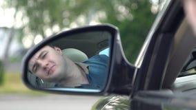 Giovane che conduce un'automobile che controlla dietro lui stock footage