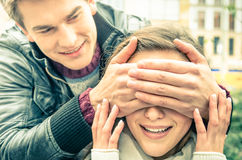 Giovane che copre gli occhi di un'amica sorpresa felice fotografia stock