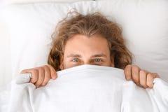 Giovane che copre il suo fronte di coperta mentre trovandosi sul cuscino bedtime immagini stock libere da diritti
