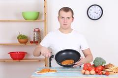 Giovane che cucina steek nella cucina Immagine Stock
