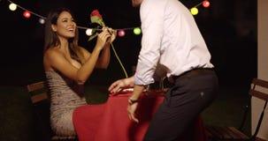 Giovane che dà ad una bella donna una rosa video d archivio