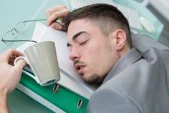 Giovane che dorme allo scrittorio Immagini Stock Libere da Diritti