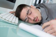 Giovane che dorme allo scrittorio Immagine Stock