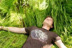 Giovane che dorme nell'erba verde lunga Fotografie Stock Libere da Diritti
